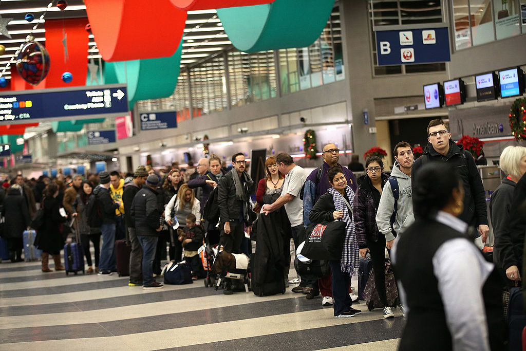 Travelers wait in line to check-in for flights at O'Hare International Airport