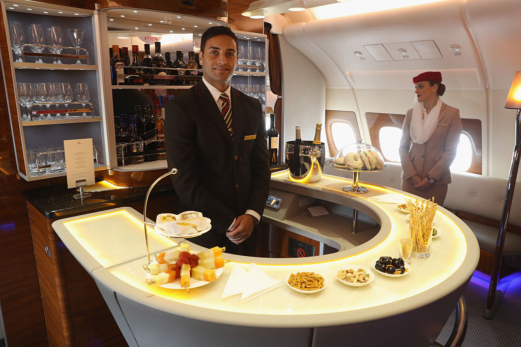 A steward and stewardess welcome visitors at the bar in business class on board an Emirates A380 passenger plane