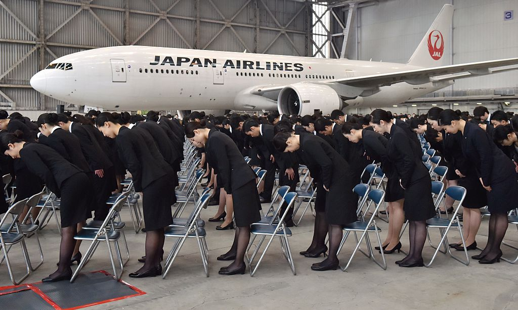 New employees of Japan Airlines Group bow their heads during their entrance ceremony