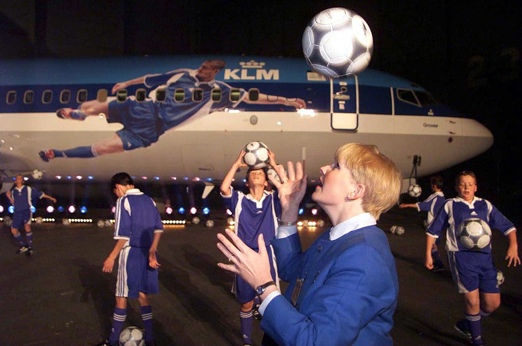 A KLM stewardess and Children play football in front of the KLM aeroplane branded for promotion of the forthcoming European Championships