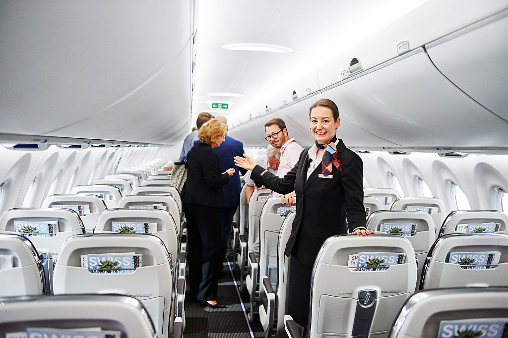 A cabin crew member welcomes guests inside Swiss International Air Lines' new Bombardier CS 100 passenger jetliner