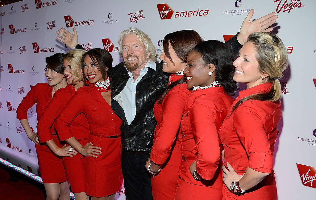 Founder and President of Virgin Group Sir Richard Branson (C) arrives with Virgin America flight attendants at The Cosmopolitan of Las Vegas