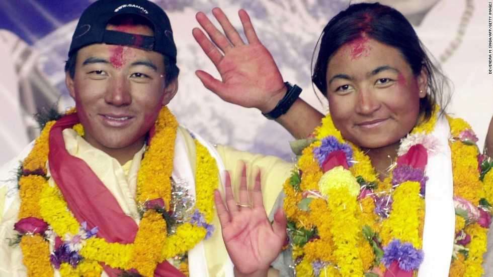 A newly married couple waves from the summit of Everest