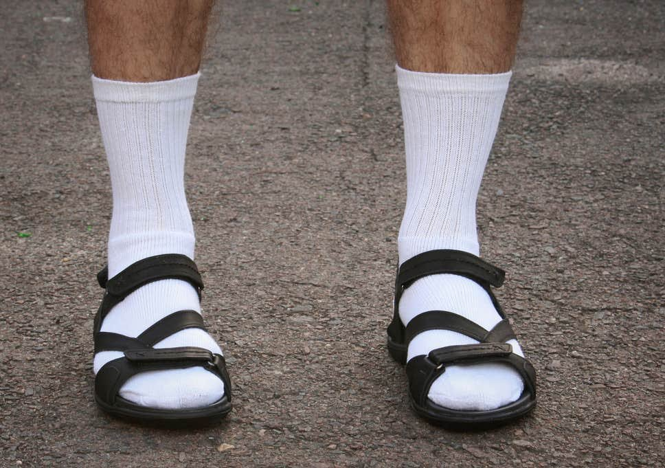 a man wearing white socks with sandals