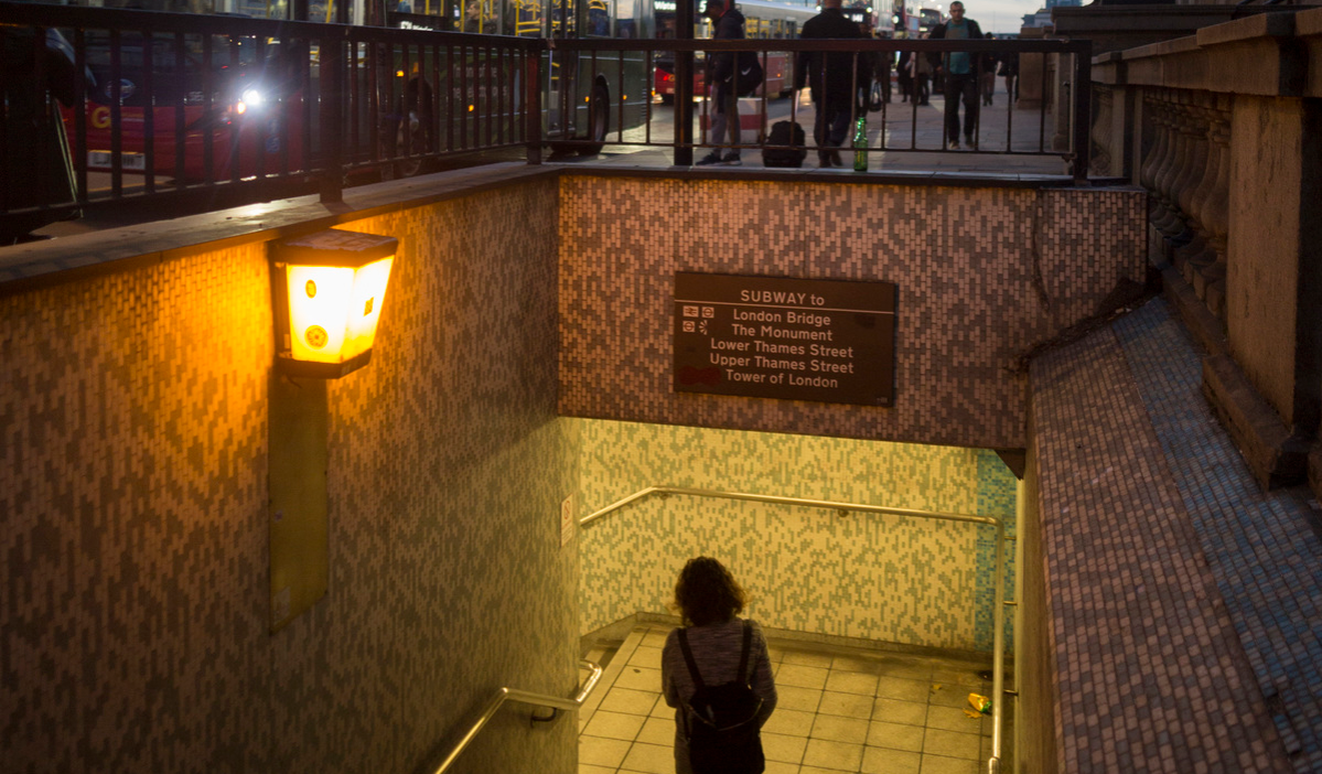 With the Shard in the background, a lady pedestrian descends steps into the tunnel under London Bridge
