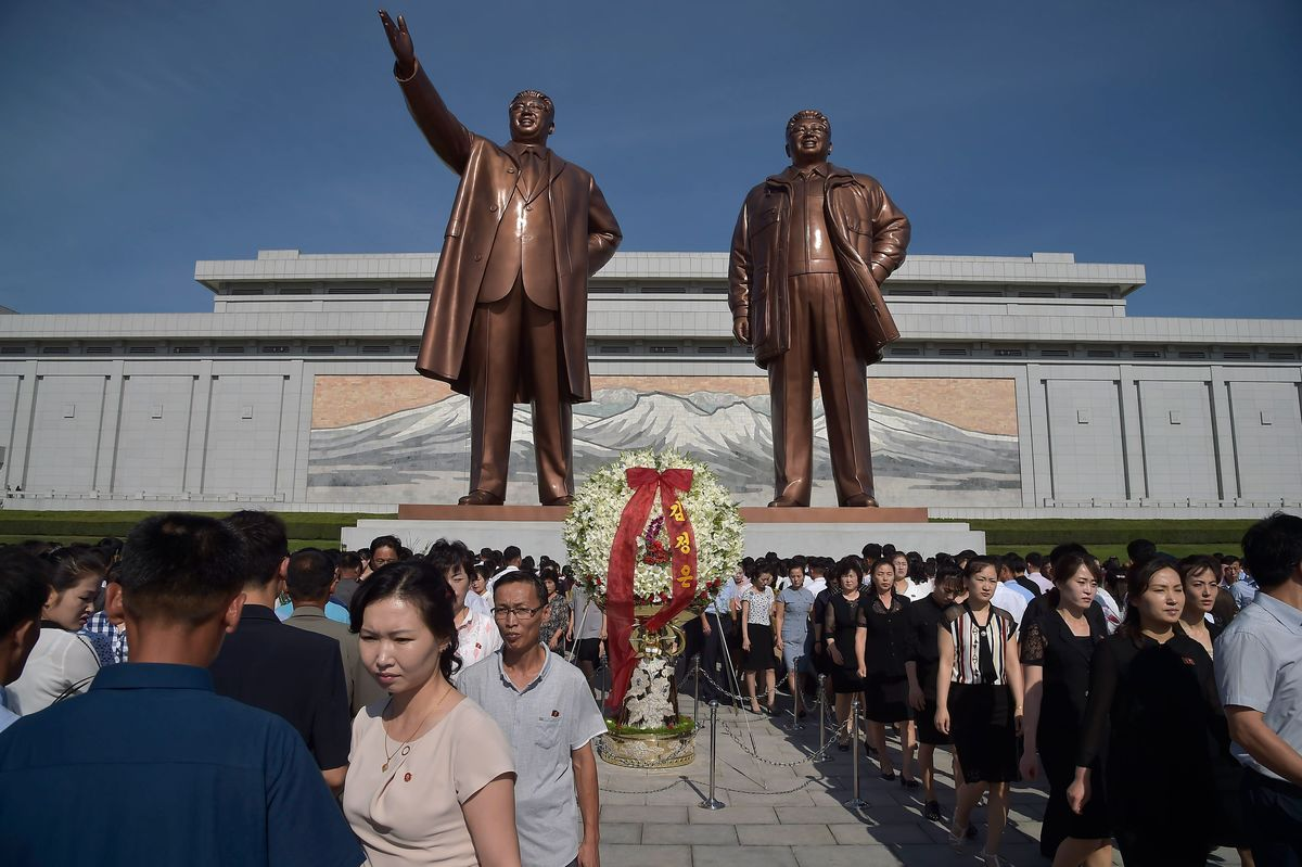 People leave after paying their respects to the late North Korean leaders Kim Il Sung and Kim Jong Il