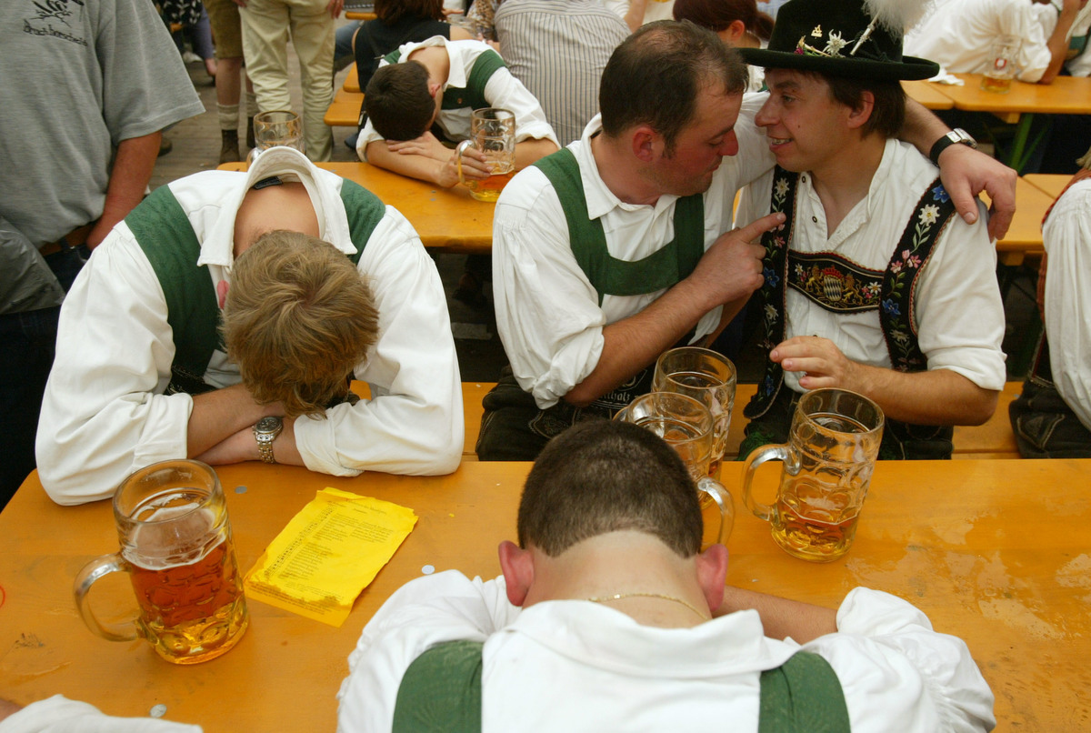 Two drunken men in traditional Bavarian outfits converse beside their passed out comrades at the annual Oktoberfest celebration September 21, 2003 in Munich, Germany.