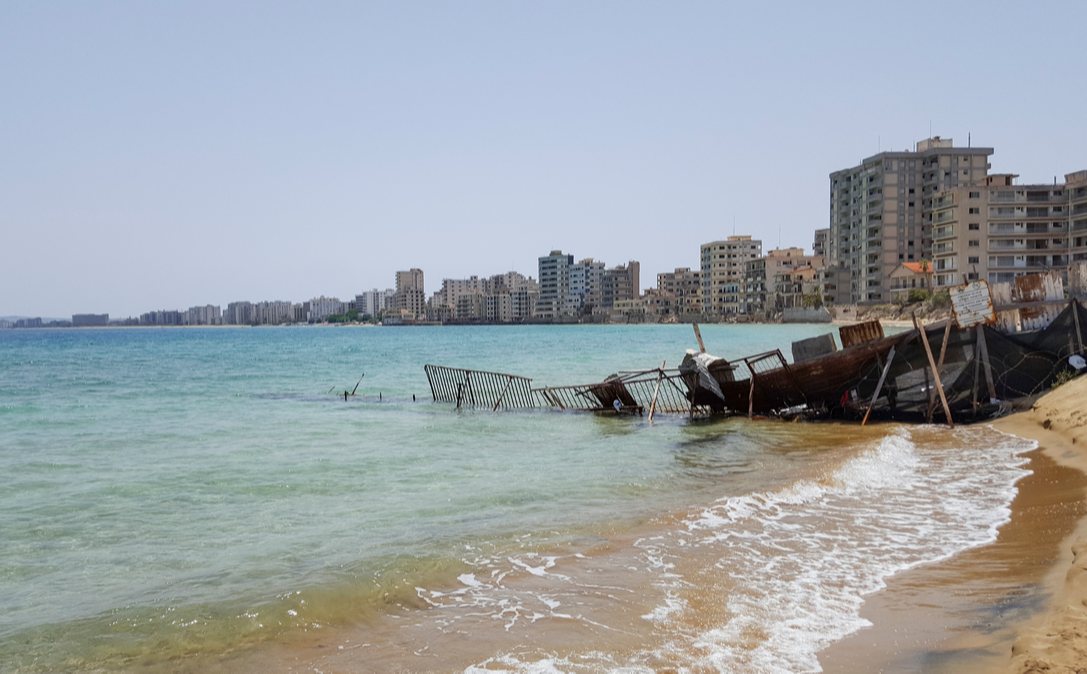 Abandoned hotel buildings stand beyond a makeshift barrier inside the 'Forbidden Zone' of Varosha, Cypress