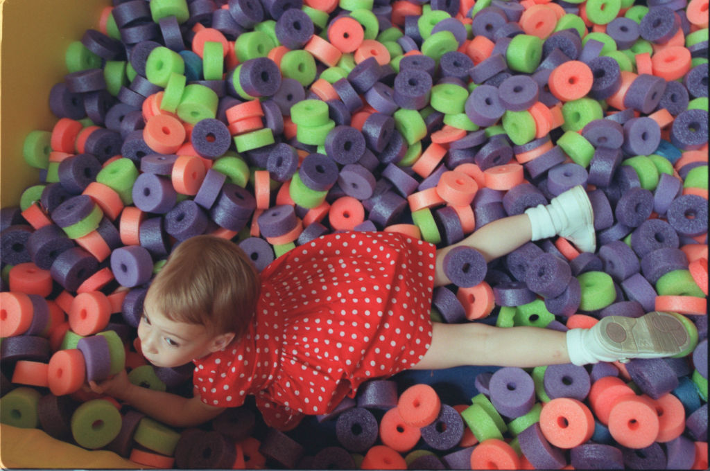 child playing in a pile of toys