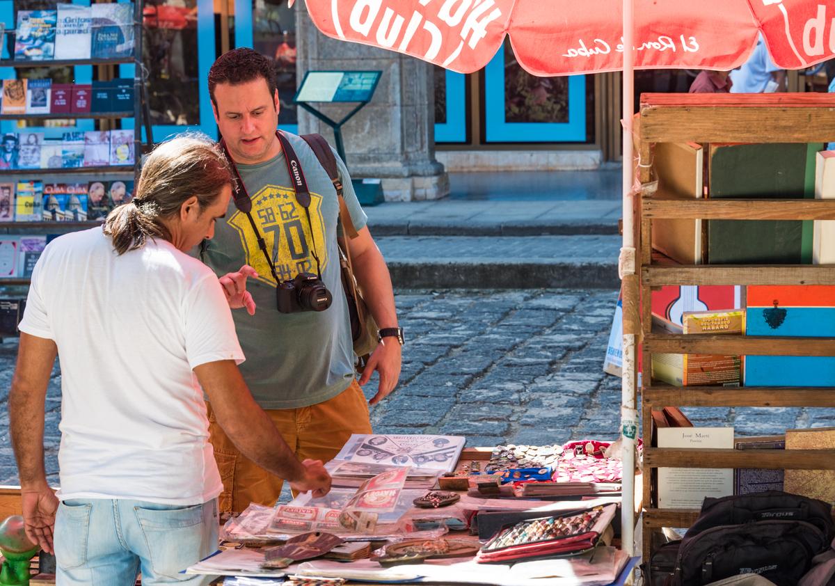 Tourist man browsing a souvenir stand in Cuba.