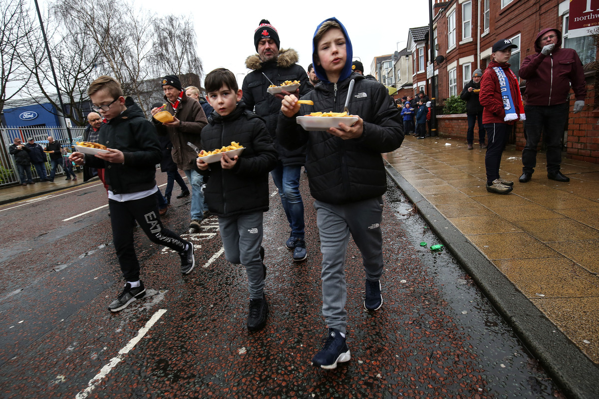 Fans walk to the match eating chips during the Premier League match between Manchester United and Huddersfield Town at Old Trafford on February 3, 2018 in Manchester, England.
