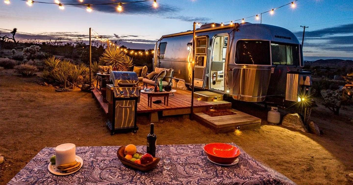 an airstream with outside furniture in joshua tree