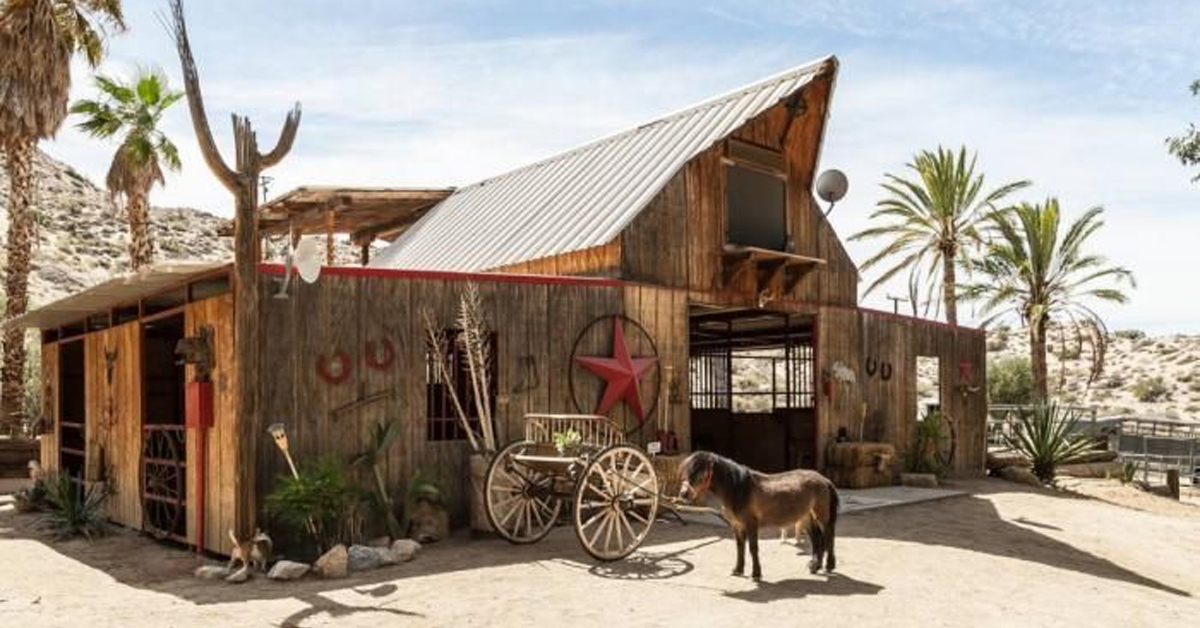 a wooden barn with palm trees and a pony