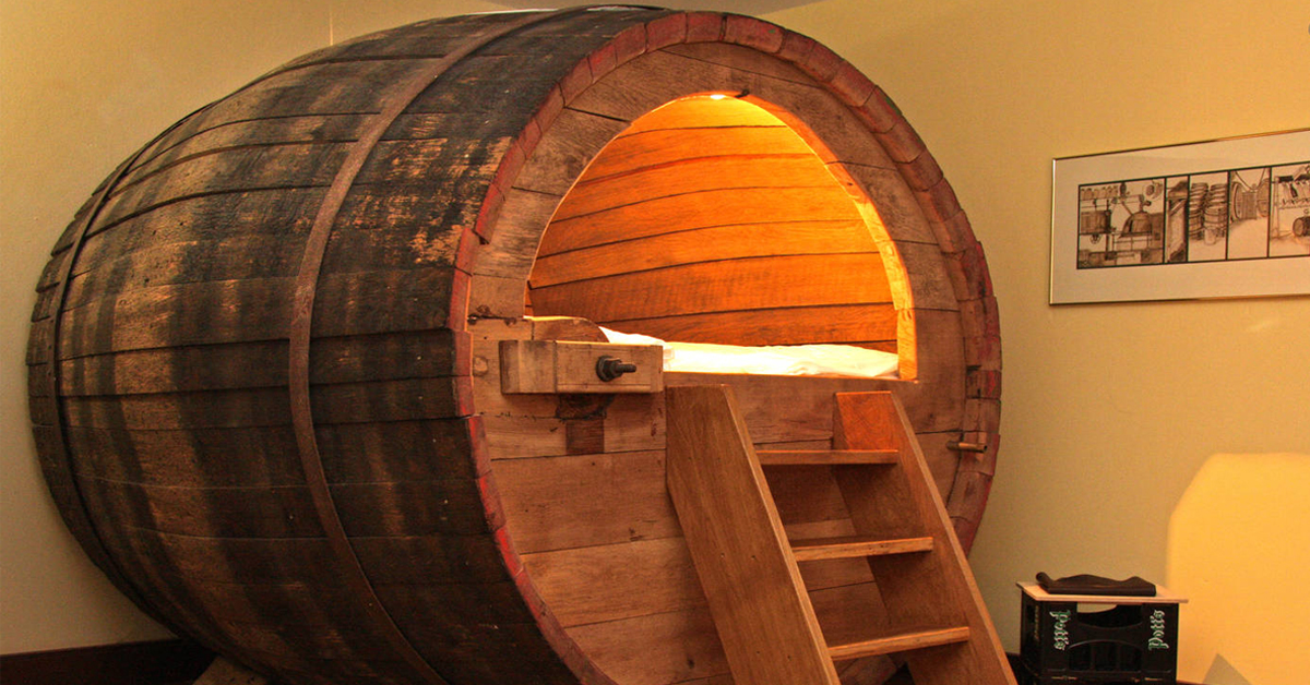 a wooden beer barrel with a bed inside