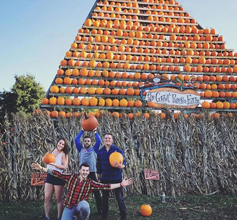 Adult friends pose in front of a tower of pumpkins
