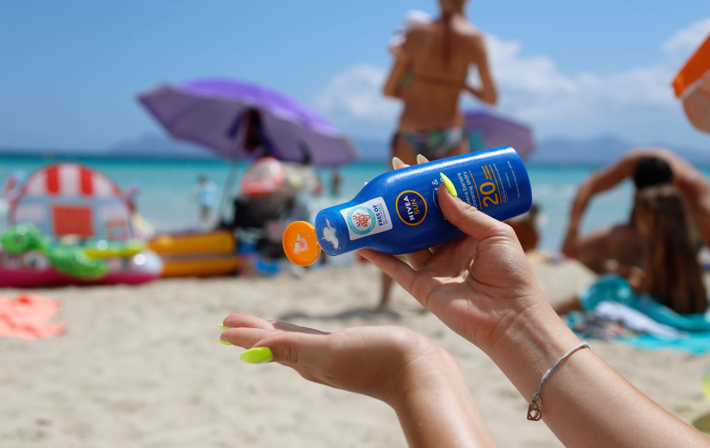 A young woman is using sunscreen on the beach
