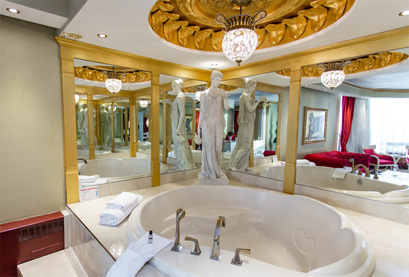A large bathtub is surrounded by golden finishings and a large statue of a woman