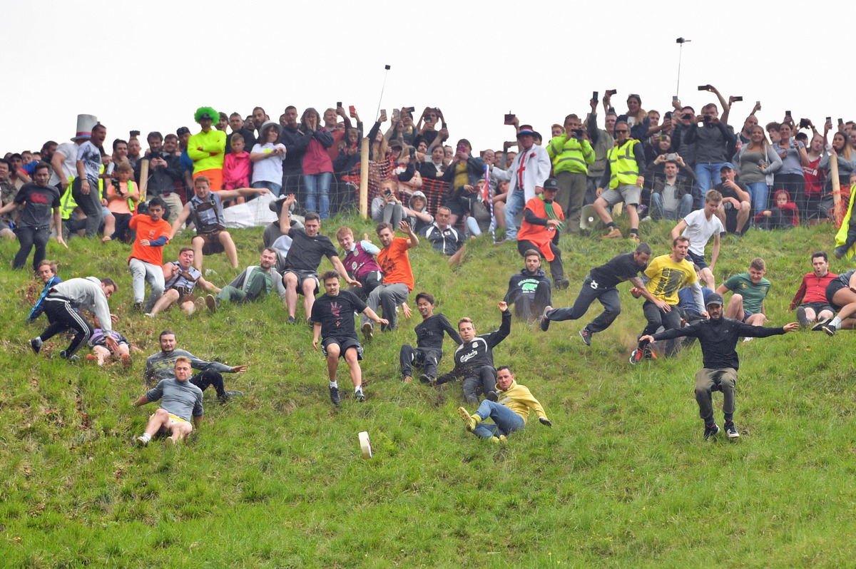 Participants chase a cheese wheel down a hill during the annual cheese rolling competition