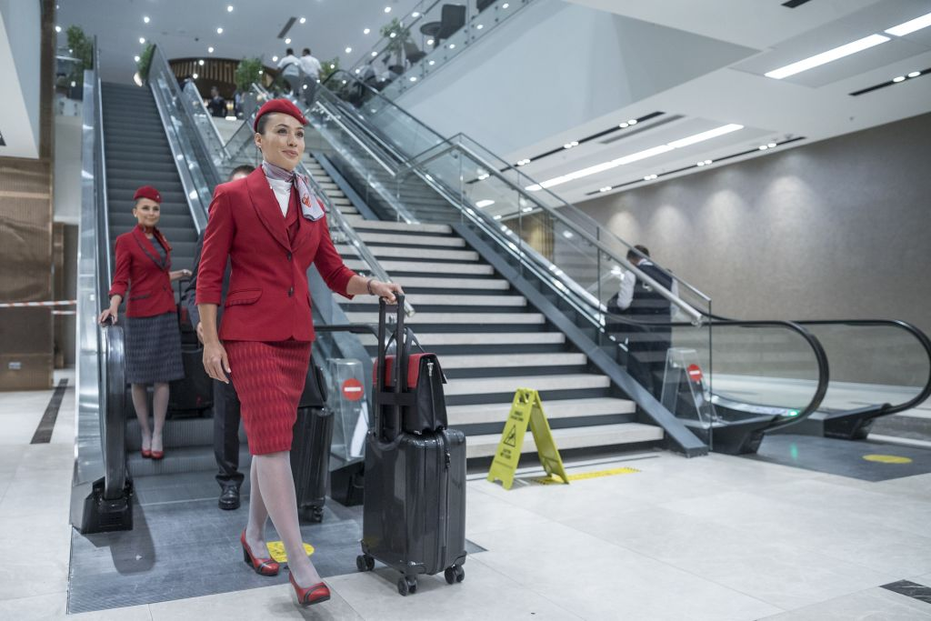 Flight Attendants Exit an Escalator