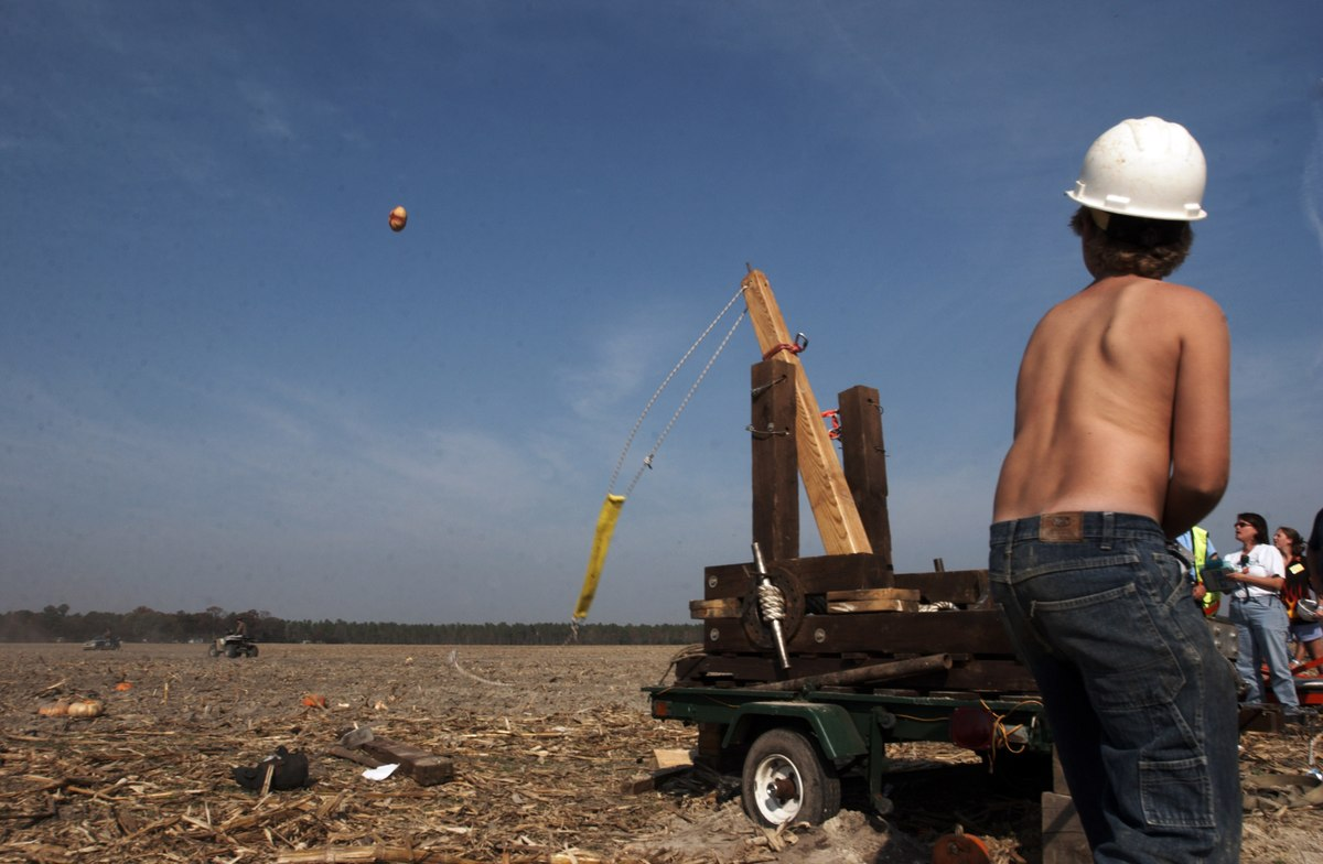 Men launch a pumpkin from a catapult during the World Championship Punkin' Chunkin' contest.