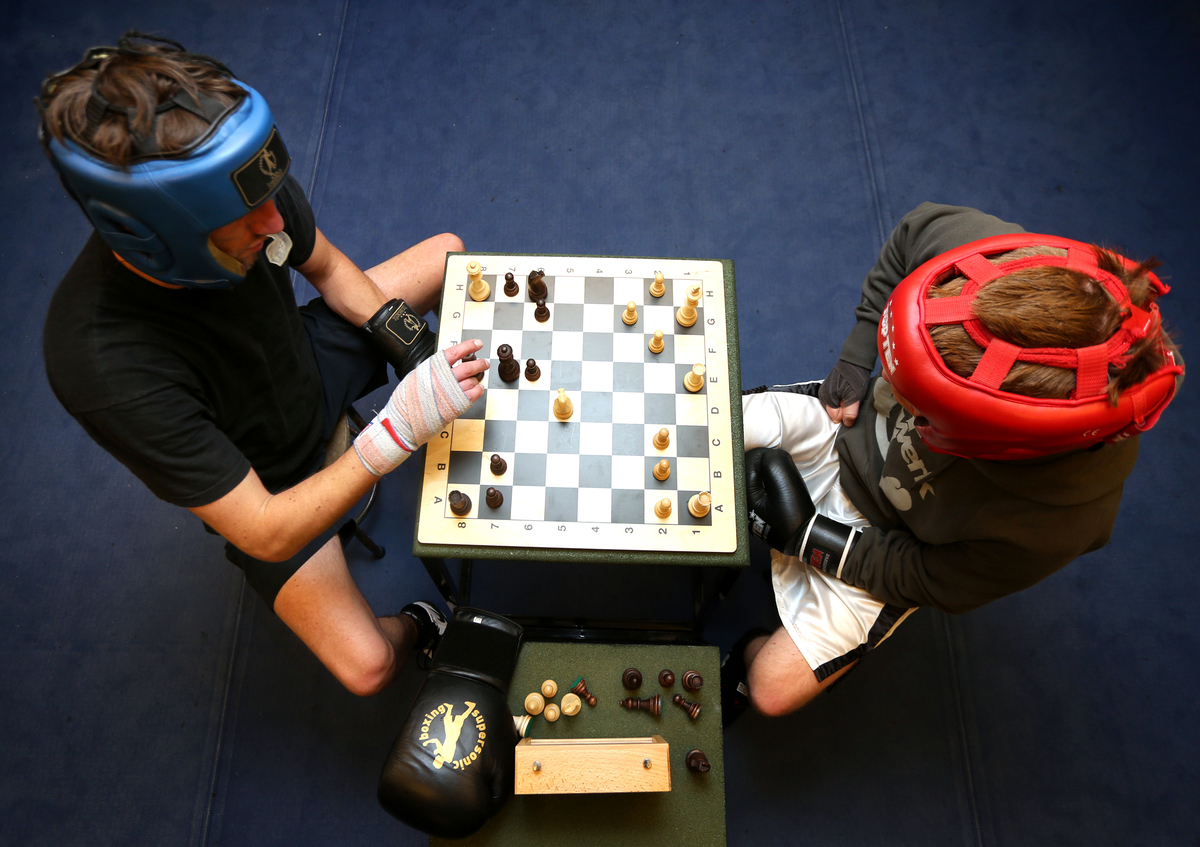 Two men play chess during a chess boxing tournament.