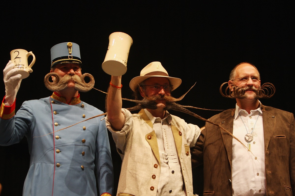 The finalists of the Sideburns Freestyle Category hold their prize mugs during the World and Moustache Championships