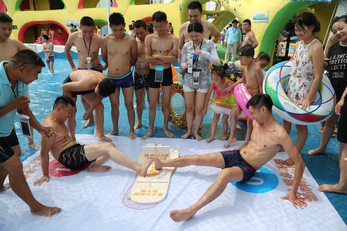 People compete in a toe wrestling competition at a water park