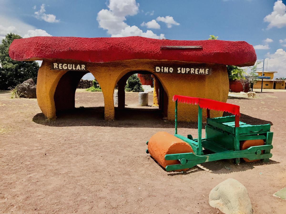 A Flinstones house and car are at Bedrock City, AZ.