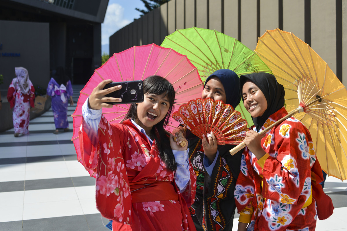 Indonesian students dressed in kimonos take a selfie in Japan.