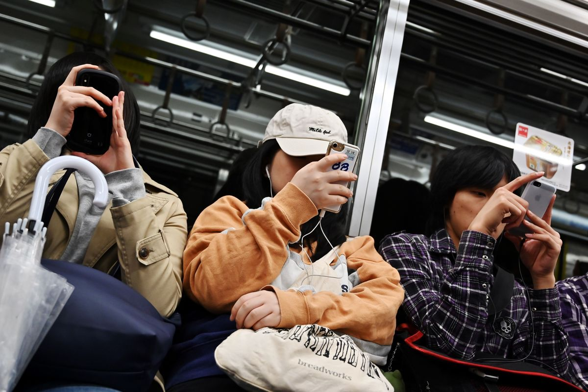 People browse their smartphones in a metro train in Tokyo.