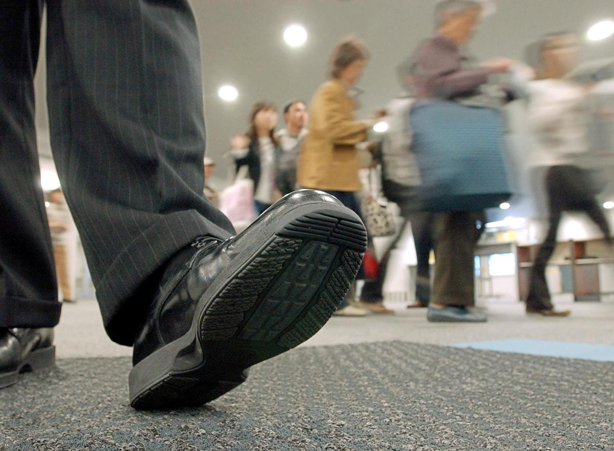 Tourists walk on a mat covered with an antiseptic solution to clean the soles of their shoes upon arrival at the Chubu International Airport in Japan.
