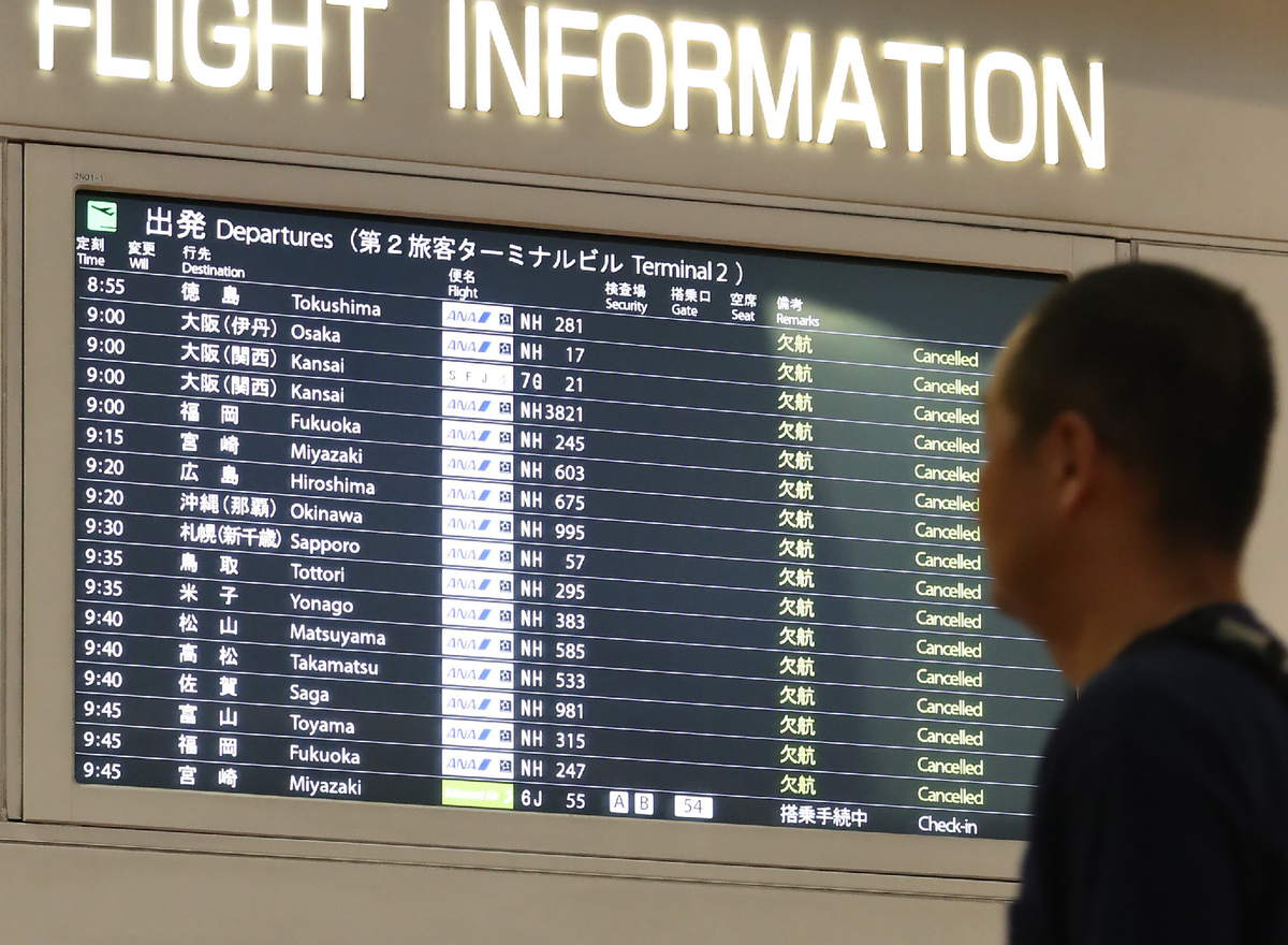 A man looks at the flight information board at the Haneda International airport in Tokyo.