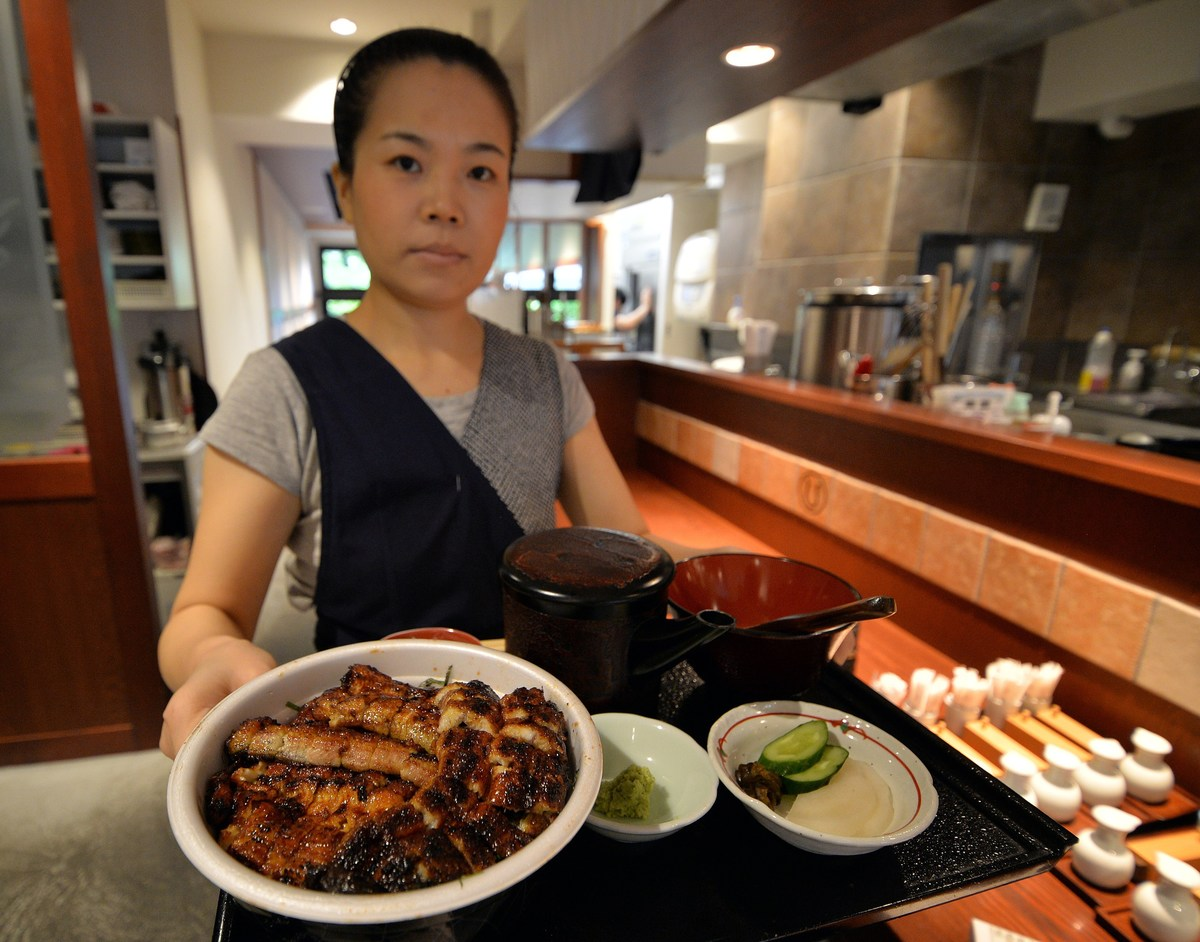 An employee of a Japanese grilled eel restaurant Unatetsu serves a dish in Tokyo.