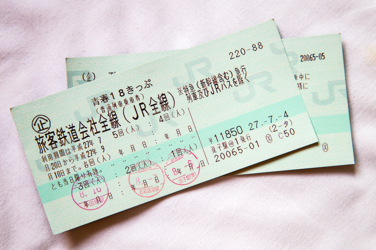 The Seishun 18 Ticket, a popular JR Japan Railway, sits on a light pink blanket.
