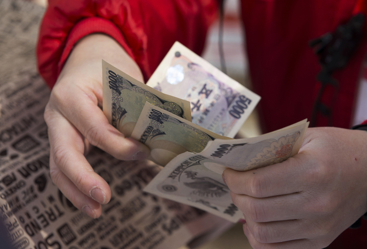 An employee counts Japanese yen notes as he sells a 'lucky bag'.