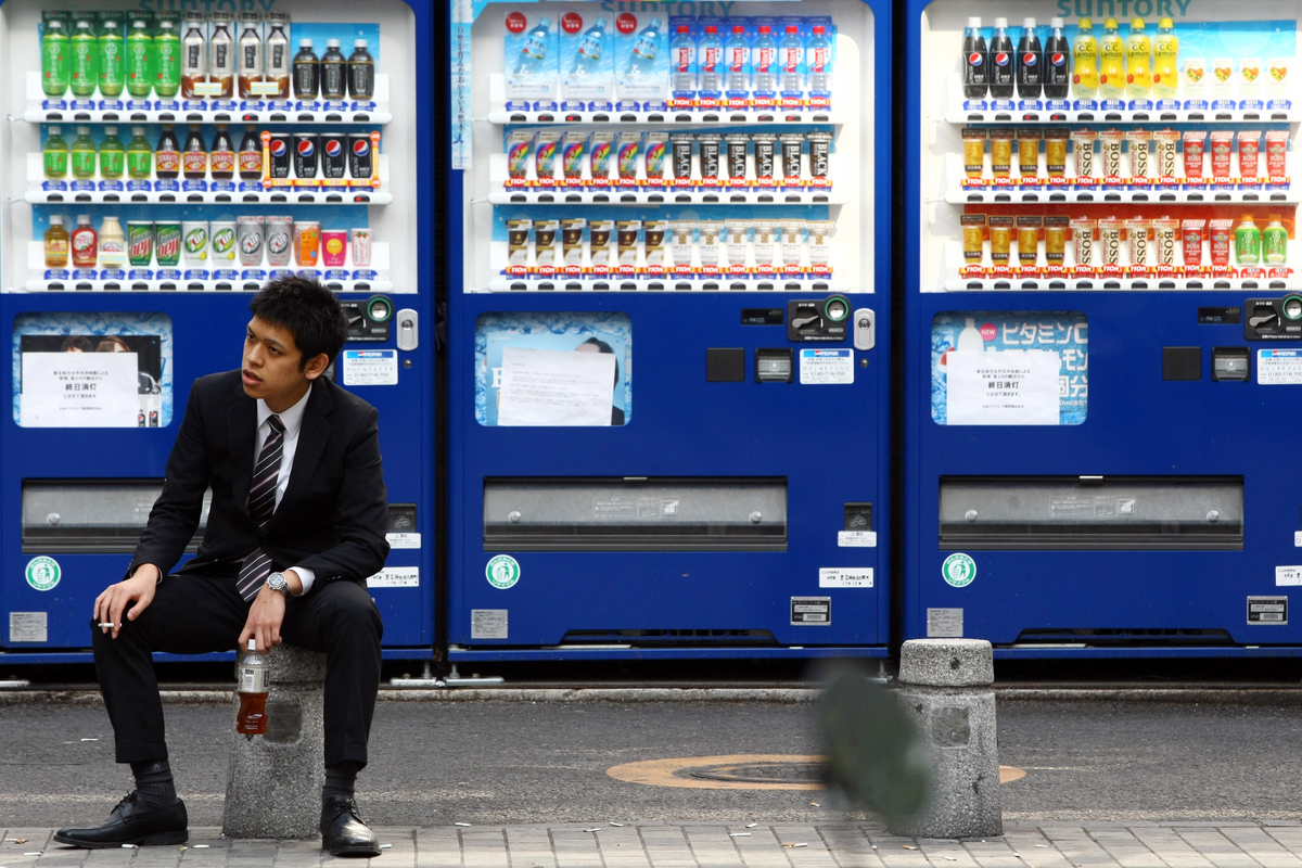 Man sits and drinks a soda that he bought from a vending machine.