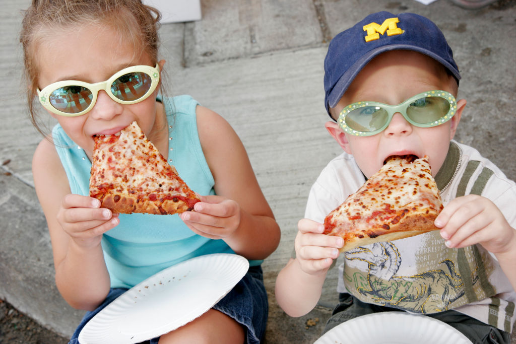 kids eating pizza on the sidewalk