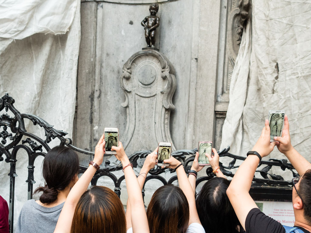 Manneken Pis Is A Tiny Statue Behind A Wall Of Tourists
