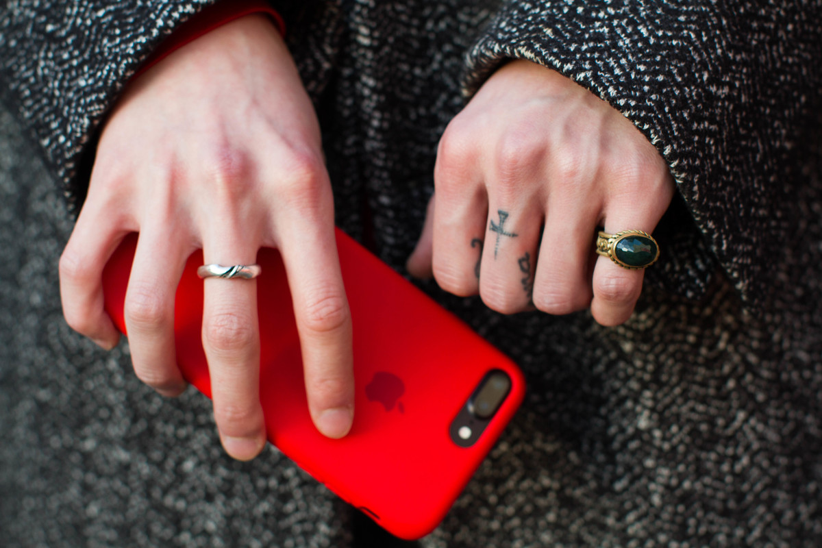 Woman holds her phones with finger tattoos on her hands in Tokyo, Japan.