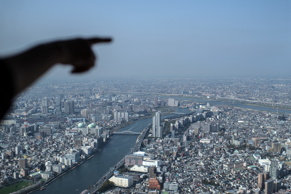 A woman points towards the Tokyo skyline from the viewing platform of the Tokyo Skytree.