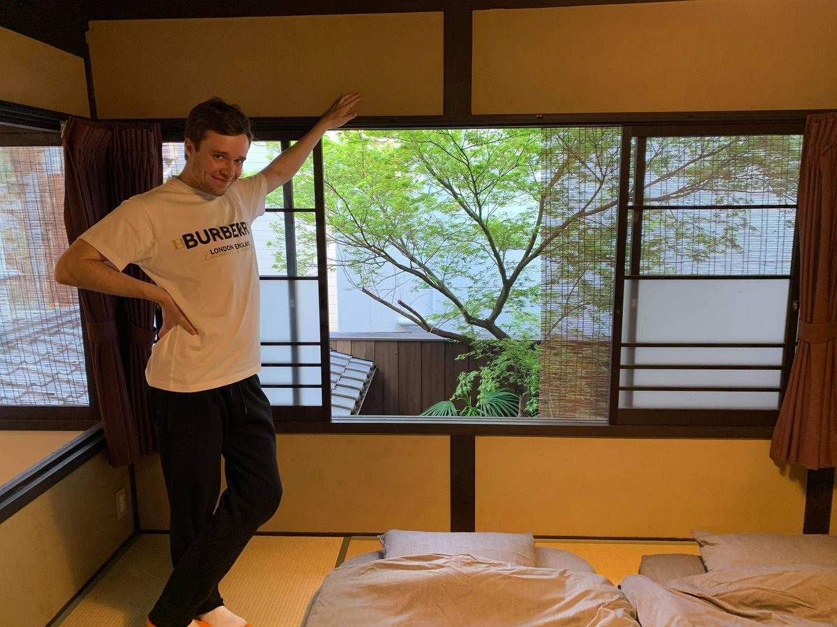 A man stands in the bedroom of his Airbnb rental in Kyoto, Japan.