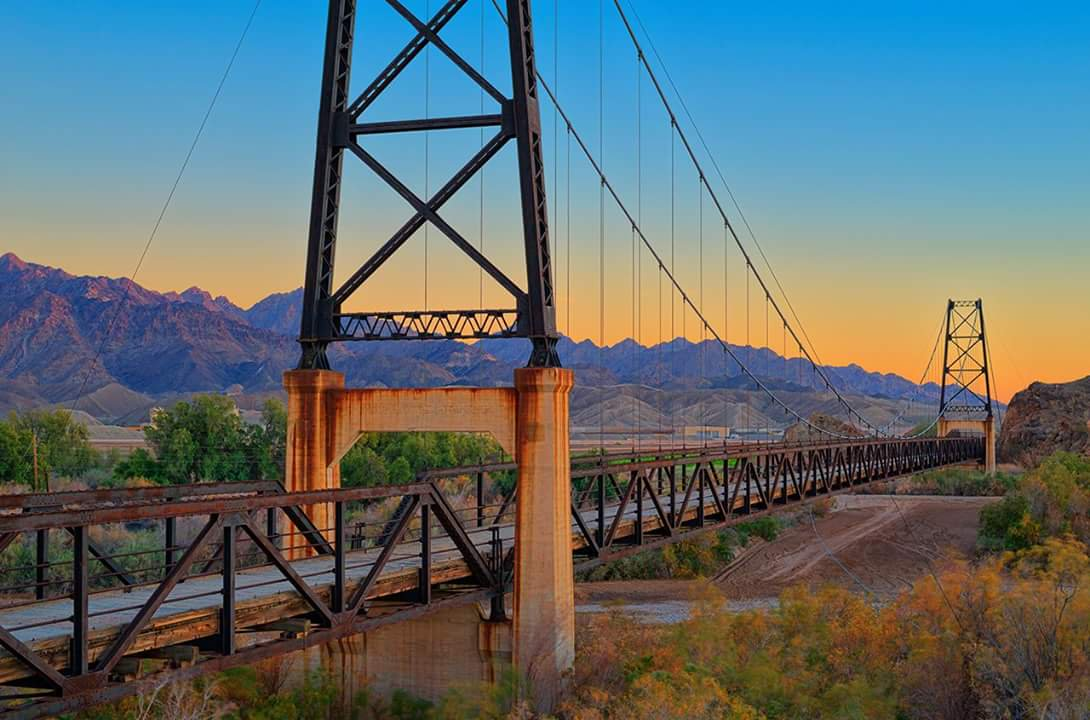 The McPhaul Suspension Bridge overhangs the Gila River in Yuma, AZ.
