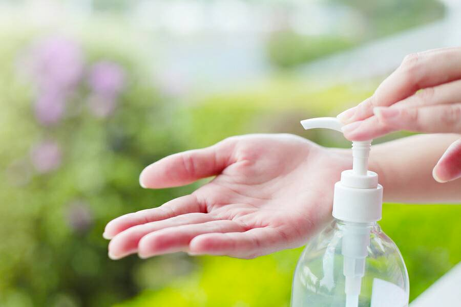 Person pours hand sanitizer in their hand.