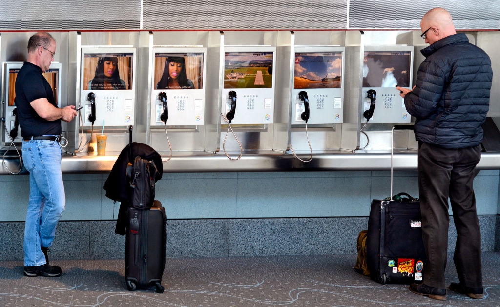 Two commercial airline passengers use their smartphones standing beside a row of landline phones