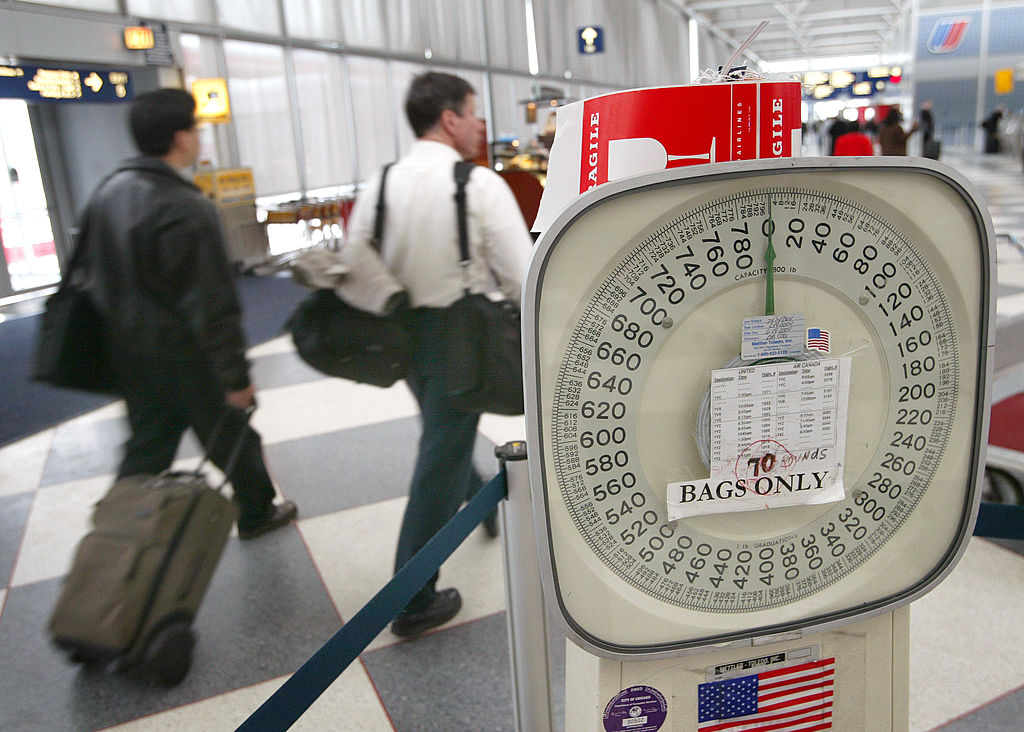 Travelers walk past a baggage scale