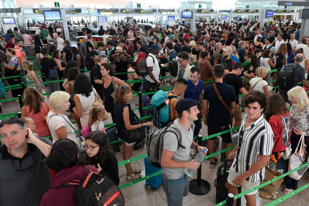 Passengers queue at El Prat airport in Barcelona