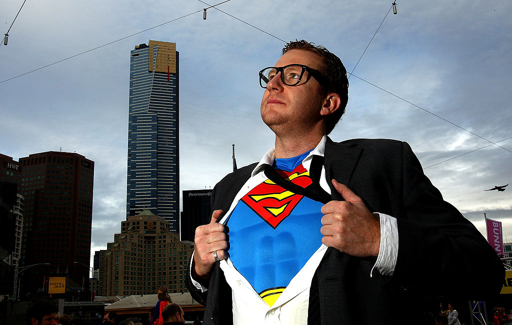 A man opens his suit to reveal a Superman costume underneath.