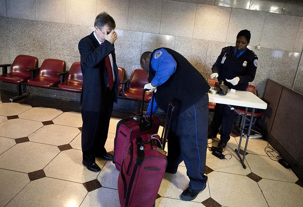A man raises a hand to his face while TSA searches his bag.