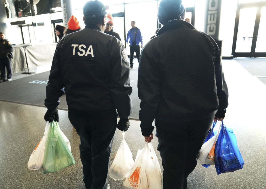 TSA workers walk out with bags in their hands.