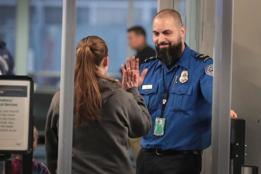 A TSA worker high fives a passenger.